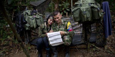 """En esta imagen, tomada el 4 de enero de 2016, Juliana, una combatiente del frente 36 de las Fuerzas Armadas Revolucionarias de Colombia, o FARC, sentada junto a su novio Alexis, en su tienda de campaña, dentro de un asentamiento clandestino en el estado de Antioquia, Colombia. """"En la guerrilla no se maneja dinero, todo nos lo dan aquí, desde medicinas a las paletas. Por eso entre nosotros no hay una relación de dependencia en la que ella espera de mí que la mantenga como es habitual en América Latina"""", dice Alexis, de 24 años. """"Entre nosotros sólo hay amor"""". Foto:AP/ Rodrigo Abd"""