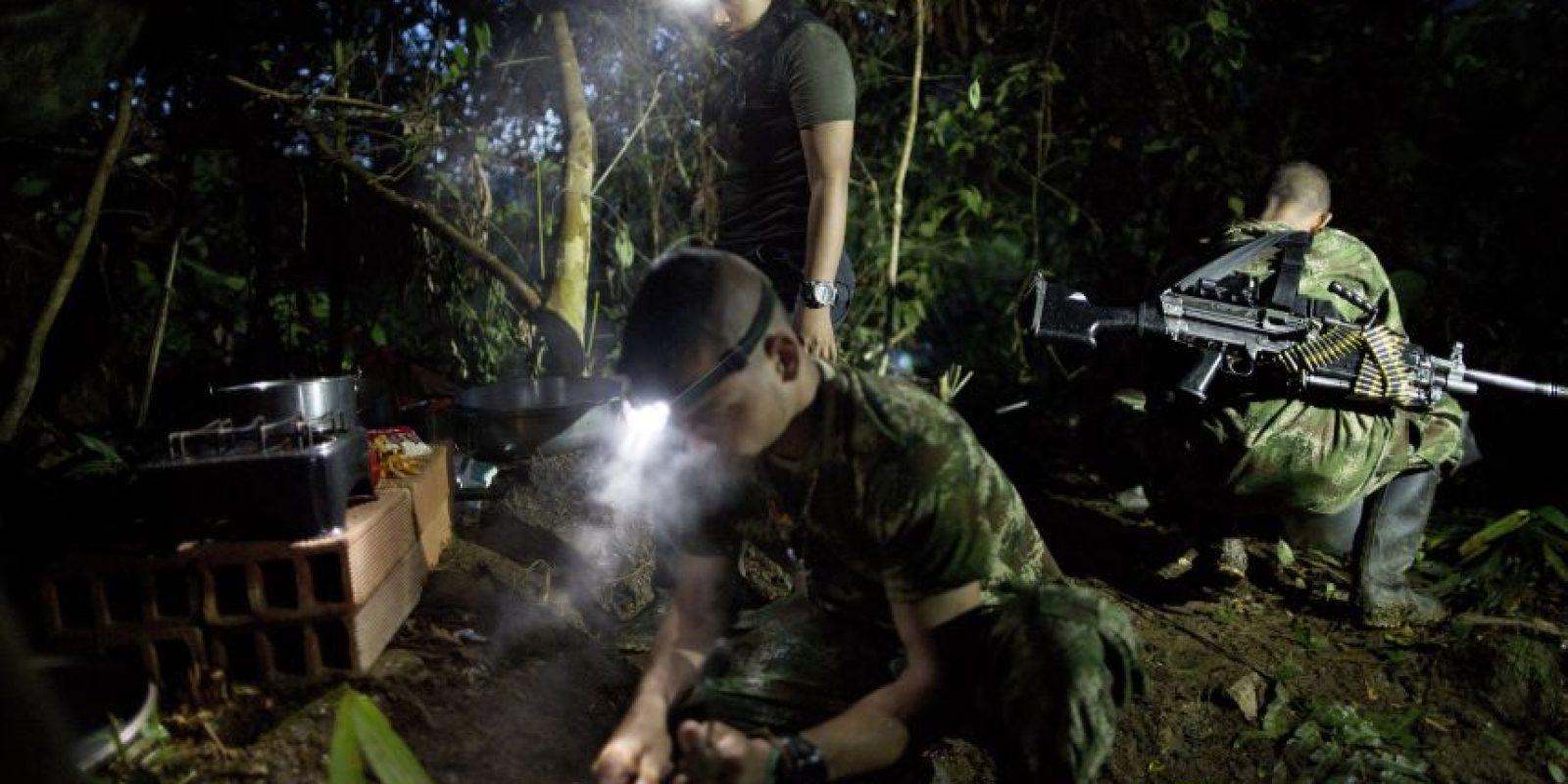 En esta imagen, tomada el 3 de enero, con la ayuda de linternas, combatientes del frente 36 de las Fuerzas Armadas Revolucionarias de Colombia, o FARC, preparan un desayuno a base de arroz, frijoles, salchichas y café, un campamento clandestino de la guerrilla en el estado de Antioquia, en el noroeste de los Alpes colombianos. La jornada comienza a las 4:30 dentro del asentamiento que comparten 22 guerrilleros rasos, 4 comandantes y dos perros. Todos colaboran en las tareas de la cocina. Foto:AP/ Rodrigo Abd