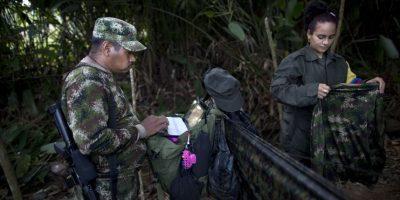 En esta imagen, tomada el 6 de enero de 2016, Juan Pablo, un comandante del frente 36 de las Fuerzas Armadas Revolucionarias de Colombia, o FARC, trabaja en su computadora portátil, junto a su novia Tania, una guerrillera de 25 años, en un campamento clandestino del grupo en el estado de Antioquia, en el noroeste de los Alpes colombianos. Foto:AP/ Rodrigo Abd