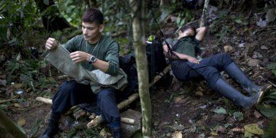 """En esta imagen, tomada el 4 de enero de 2016, Oscar, un guerrillero del frente 36 de las Fuerzas Armadas Revolucionarias de Colombia, o FARC, remienda un par de pantalones mientras su """"socia"""" Gisell descansa en una hamaca, en un campamento clandestino de la guerrilla en el estado de Antioquia, en el noroeste de los Alpes colombianos. Dentro de la organización se refieren a las parejas con el término """"socia"""" porque no se pueden ofrecer riquezas materiales. Foto:AP/ Rodrigo Abd"""