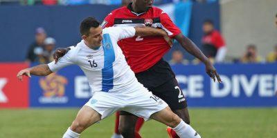 Marco Pappa pelea la pelota con un jugador trinitario. Foto:AFP
