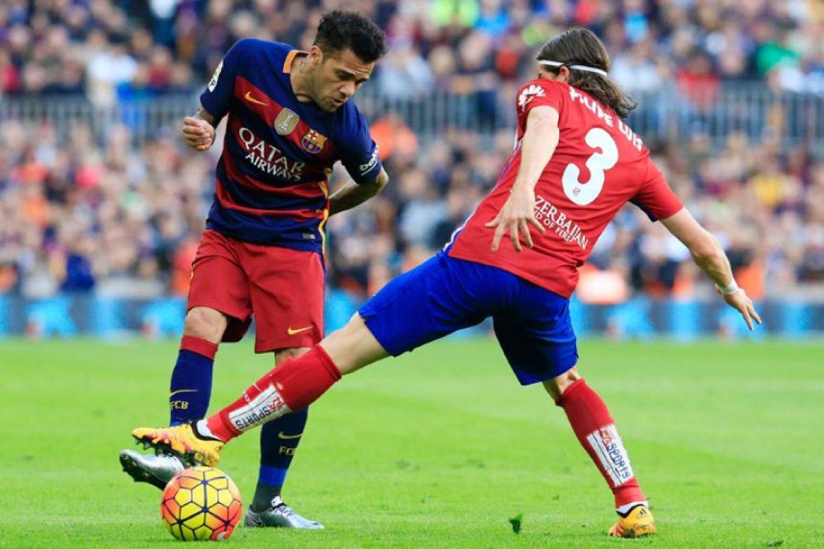 Dani Alves trata de evadir la marca de su compatriota Filipe Luis. Foto:AFP
