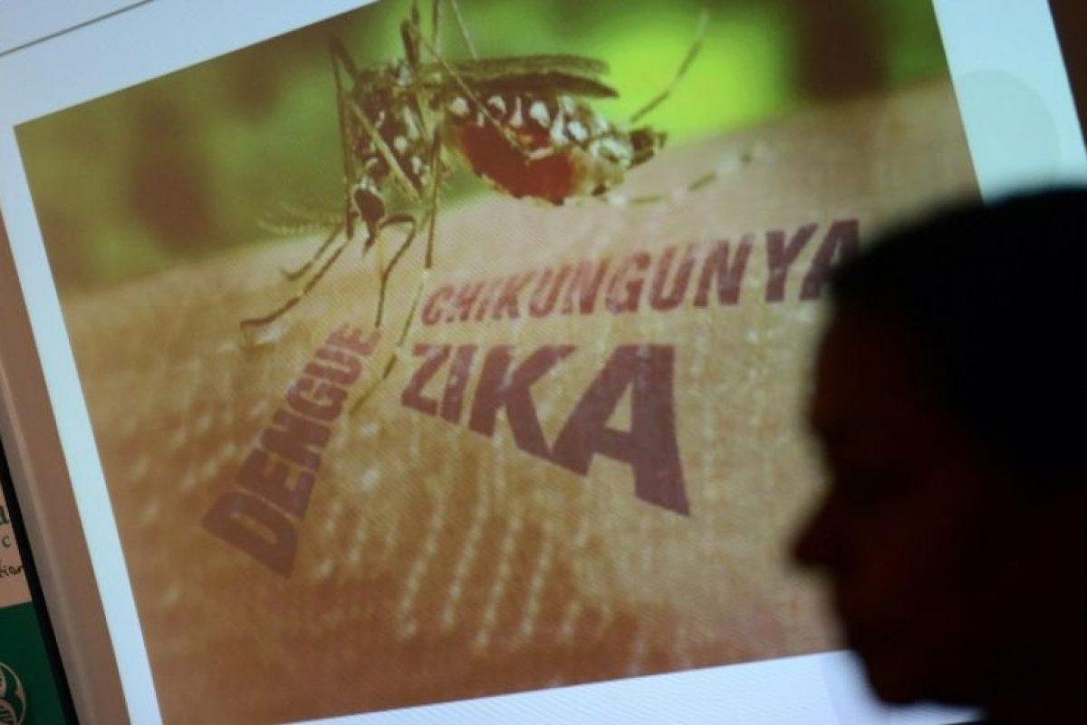 Una persona camina junto a un póster advirtiendo sobre el virus del Zika en India. Foto:AFP
