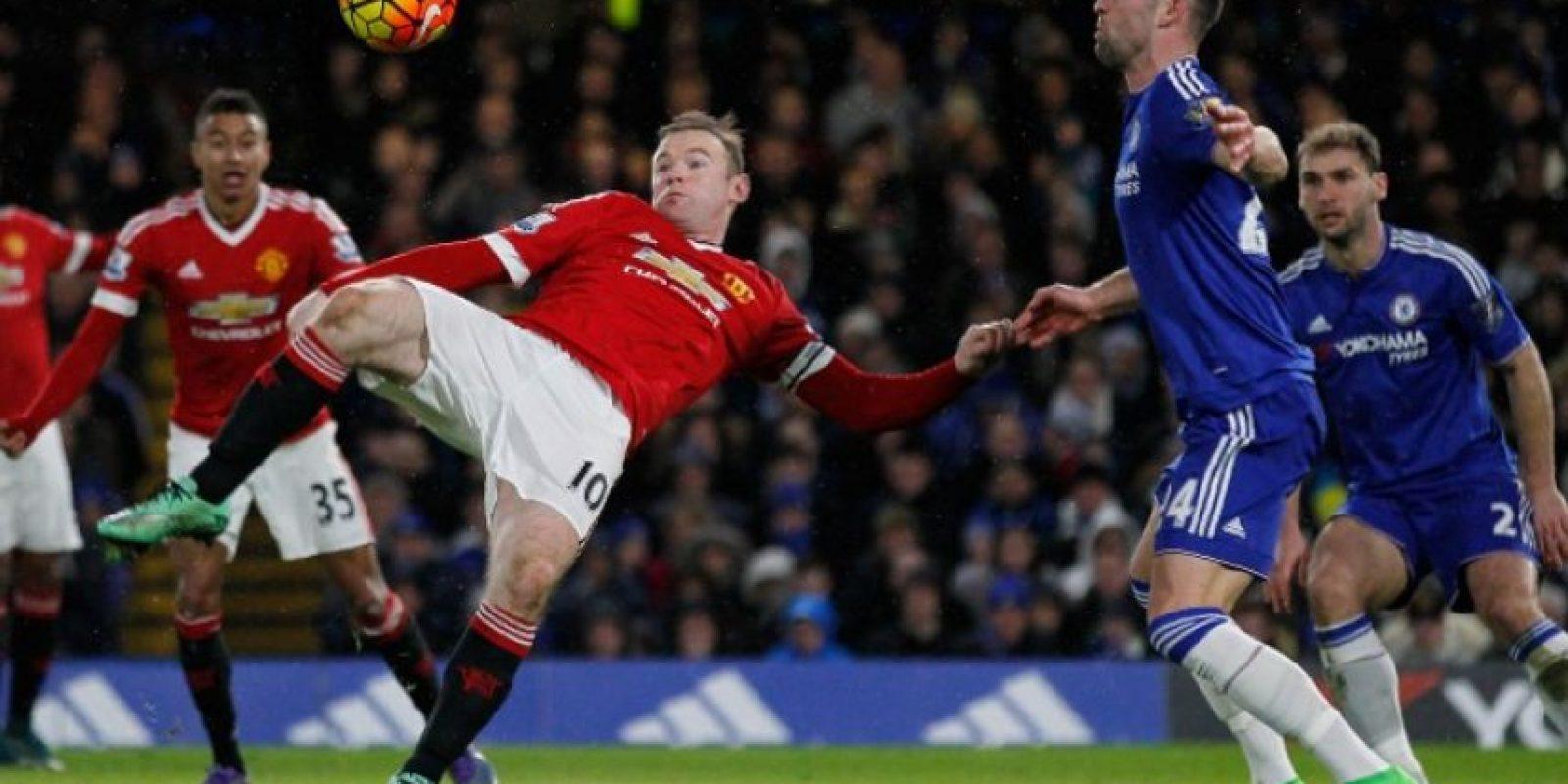 Wayne Rooney, del Manchester United, se prepara para hacer un remate, frente a Gary Cahill, del Chelsea. Foto:AFP