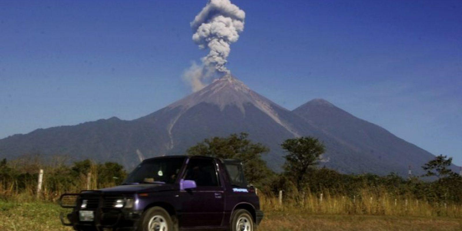 Un vehículo transita en una carretera de Guatemala, con el volcán de Fuego de fondo. Foto:AFP