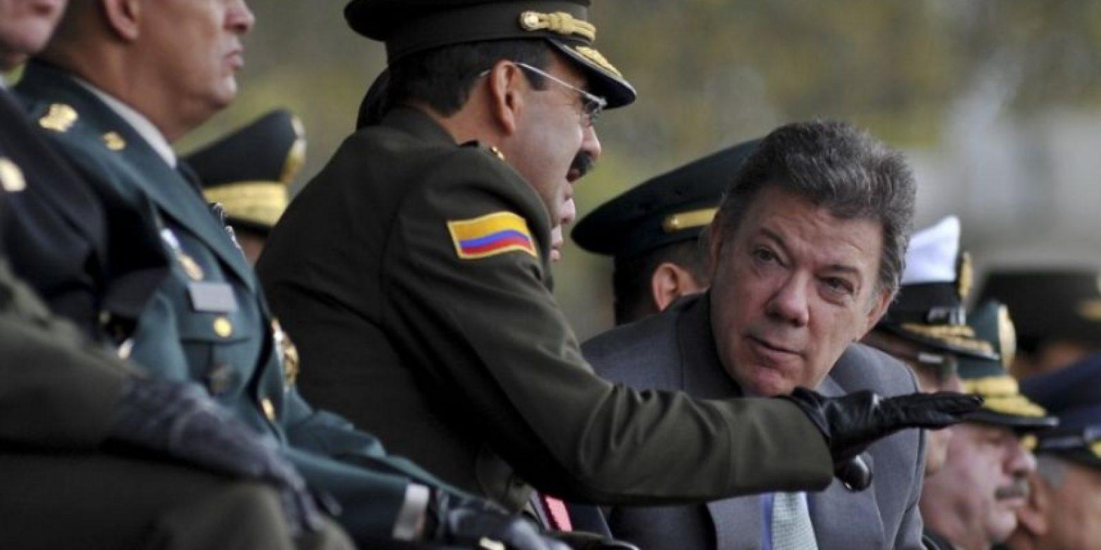 El director de la Policía de Colombia, Rodolfo Palomino (centro), conversa con el presidente Juan Manuel Santos (derecha). Foto:AFP