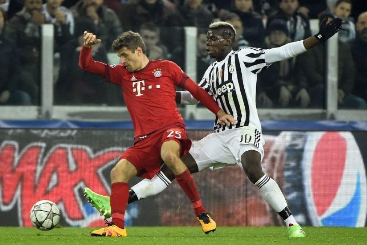 Paul Pogba y Tomas Müller disputan un balón en un partido de Champions League. Foto:AFP