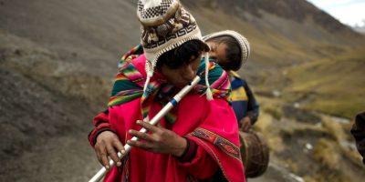 En esta fotografía del 24 de mayo de 2016 un peregrino que lleva a su hijo en la espalda toca una flauta andina tradicional conocida como quena mientras camina al santuario del Señor de Qoyllur Rit'i para tomar parte en el festival sincrético del mismo nombre, traducido de la lengua quechua como Estrella de Nieve, en el Valle Sinakara en la región peruana de Cusco. Foto:AP Photo/ Rodrigo Abd