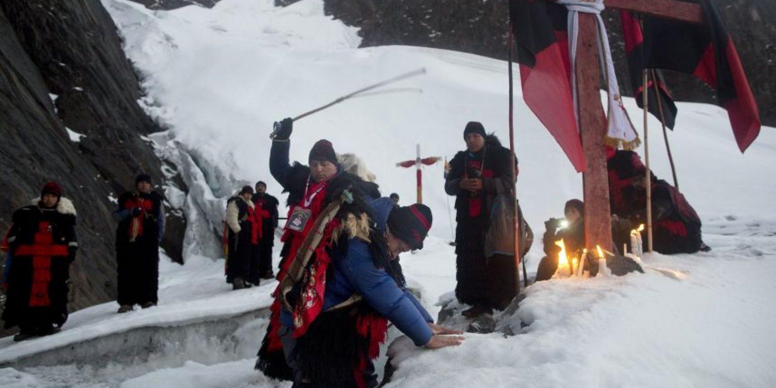 """En esta fotografía del 24 de mayo de 2016 un """"ukuku"""", que representa a una criatura mítica mitad hombre mitad oso, coloca sus manos sobre el hielo del glaciar de la montaña Qullqip'unqu de rodillas ante una cruz mientras es azotado por un líder """"ukuku"""" en una ceremonia de inducción, como parte del sincrético festival de Qoyllur Rit'i traducido de la lengua quechua como Estrella de la Nieve en el Valle Sinakara, en la región de Cusco en Perú. Los nuevos reclutas prometen hacer la peregrinación tres años consecutivos. Foto:AP Photo/ Rodrigo Abd"""
