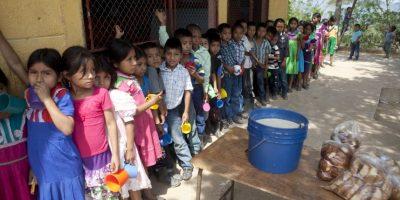 En esta fotografía del 31 de mayo de 2016, estudiantes esperan que les llenen su taza con atole, una bebida a base de maíz, y les entreguen un pedazo de pan antes de iniciar con su jornada escolar en el pueblo de Las Flores, en el estado oriental Chiquimula en Guatemala. Históricamente afectados por la pobreza, miles de habitantes del este de Guatemala padecen una prolongada sequía que ha derivado en una crisis alimentaria. Foto:Moises Castillo/ AP