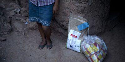En esta fotografía del 30 de mayo de 2016, Andrea García se para a un lado de una donación de Oxfam de semillas de maíz resistentes a la sequía y decenas de bolsas de harina de maíz en San Juan Ermita, en el estado oriental Chiquimula en Guatemala. Históricamente afectados por la pobreza, miles de habitantes del este de Guatemala padecen una prolongada sequía que ha derivado en una crisis alimentaria. Foto:Moises Castillo/ AP