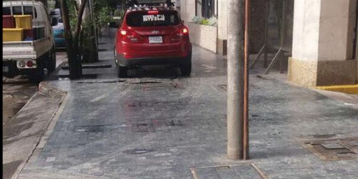 Conductor se equivoca de parqueo y se estaciona sobre la banqueta