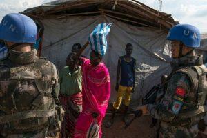 Foto tomada el 3 de septiembre de 2016 muestra a una persona desplazada de su hogar transportando alimentos en su cabeza entre tropas de mantenimiento de la paz de la ONU, durante una barrera de seguridad para la visita de alto nivel de una delegación del organismo, en Juba. Foto:CHARLES ATIKI LOMODONG/afp.com