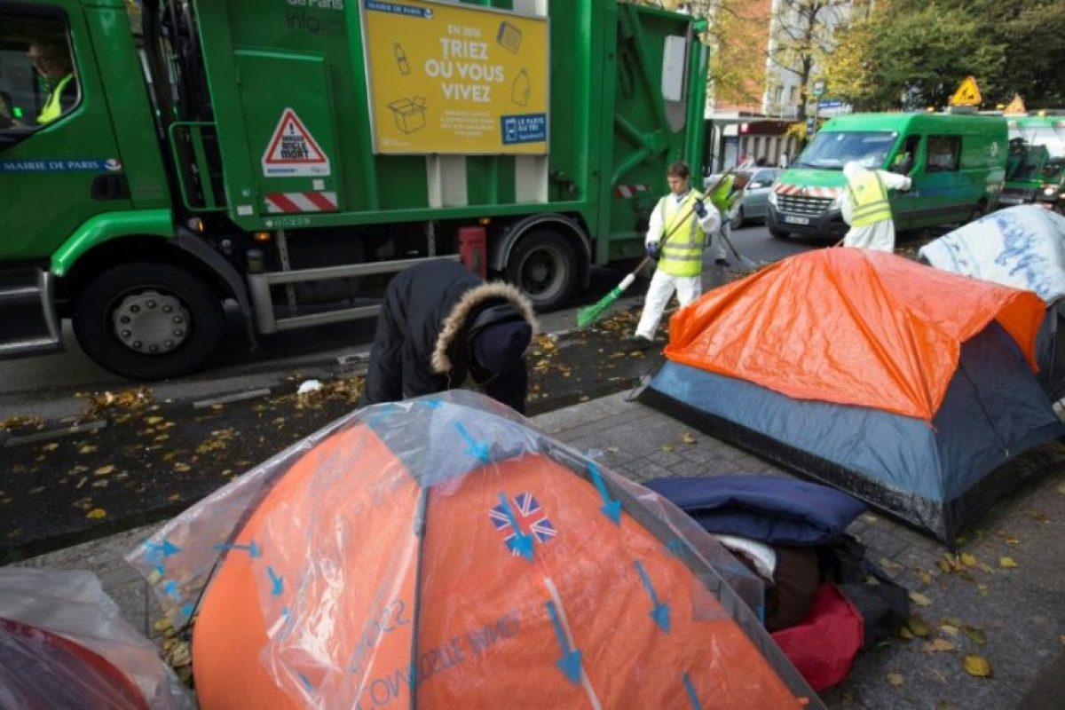 Trabajadores municipales limpian la calle cerca de tiendas de campaña, el 28 de octubre de 2016, en París, donde se instalaron migrantes que viven en condiciones miserables. Foto:JOEL SAGET/afp.com