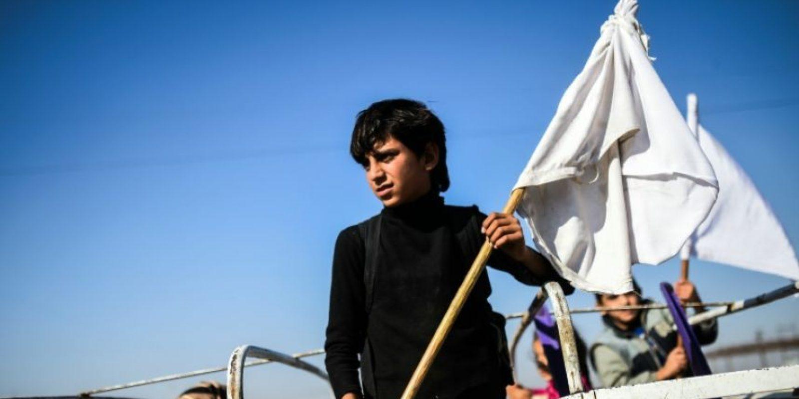 Un niño sostiene una bandera blanca a bordo de un camión que se dirige a campos para personas desplazadas por los combates entre yihadistas y fuerzas gubernamentales, el viernes 4 de noviembre cerca del pueblo de Gogjali, al este de Mosul, en Irak Foto:Bulent Kilic/afp.com