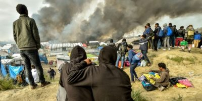 Dos migrantes observan juntos el humo de los incendios provocados en el campamento de la 'Jungla', en Calais, norte de Francia, el 26 de octubre de 2016 Foto:Philippe Huguen/afp.com