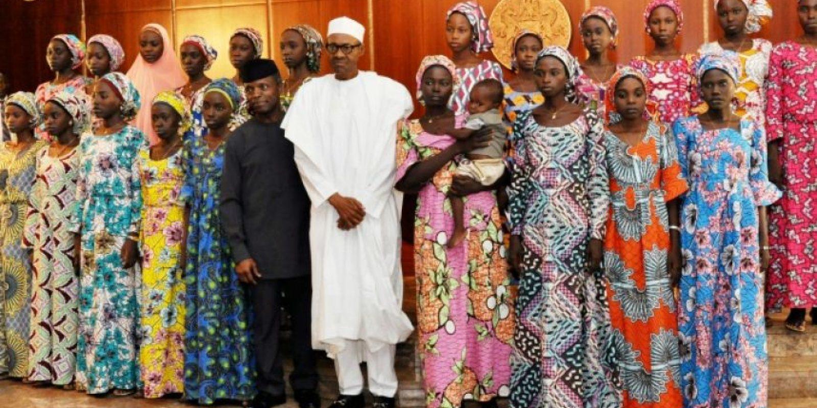 El presidente nigeriano Muhammadu Buhari (C) posa el 19 de octubre de 2016 con las 21 chicas Chibok que fueron liberadas por Boko Haram la semana pasada tras largo cautiverio, en la casa de gobiernol en Abuja, Nigeria. Foto:Philip OJISUA/afp.com