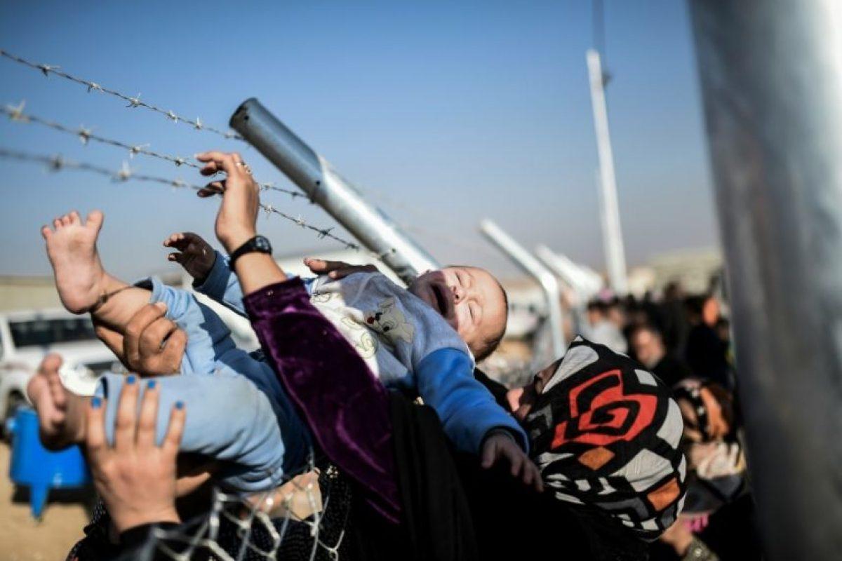 Un bebé es pasado por encima de la valla a su madre luego de ser mostrado a la familia que llegó de visita a un campo de refugiados en Khazir el 5 de noviembre de 2016 Foto:Bulent Kilic/afp.com