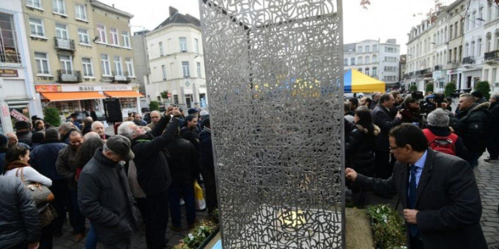 """Peatones contemplan la obra de arte """"Llama de la Esperanza"""" después de que funcionarios desvelaran la escultura en memoria de las víctimas de los atentados terroristas en París y Bruselas en el distrito de Molenbeek, en Bruselas, el 8 de noviembre de 2016. Foto:EMMANUEL DUNAND/afp.com"""