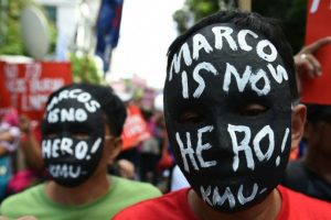 Dos jóvenes llevan máscaras con la leyenda 'Marcos no es un héroe' durante una manifestación frente a la sede de la Corte Suprema de Filipinas, este martes 8 de noviembre en Manila Foto:Ted Aljibe/afp.com