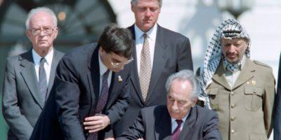 Simon Peres firma los acuerdos de Oslo ante el presidente de EEUU, Bill Clinton, el primer ministro israelí, Isaac Rabin (izq), y el líder palestino, Yaser Arafat, el 13 de septiembre de 1993 en una ceremonia en la Casa Blanca, en Washington Foto:J. David Ake /afp.com