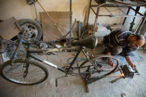El mecánico sirio Abu Rahmo hace girar un dinamo en una vieja bicicleta para generar energía el 31 de octubre de 2016 en el asediado barrio de Ansari, en Alepo Foto:Karam Al Masri/afp.com