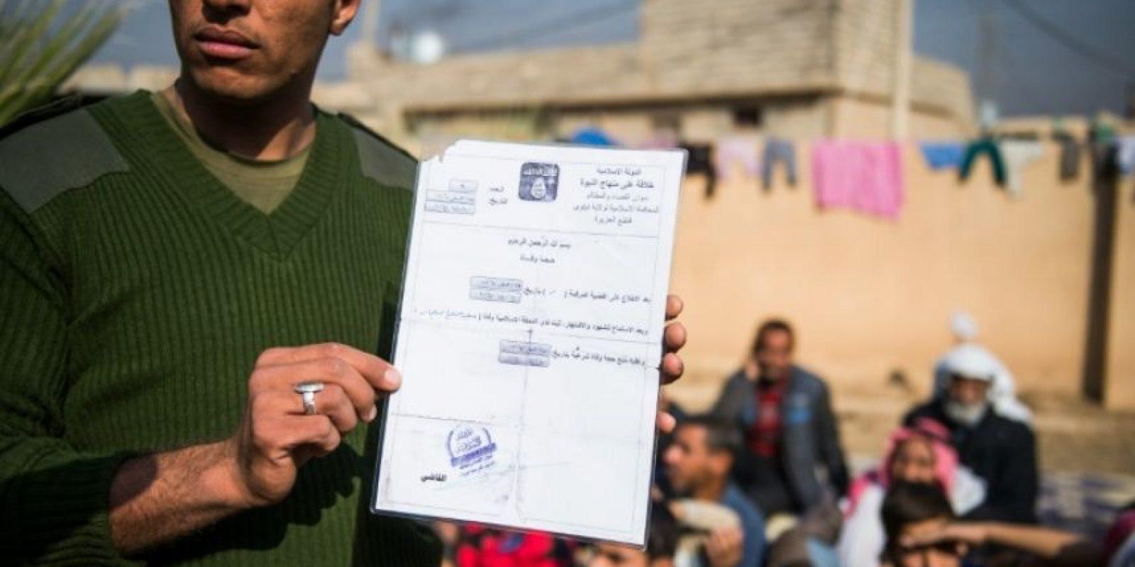 Un soldado de la novena división armada del ejército iraquí sostiene un certificado de defunción expedido por Estado Islámico, cerca de una base adyacente al barrio de Al-Intissar en Mosul, el 7 de noviembre de 2016 Foto:Odd Andersen/afp.com