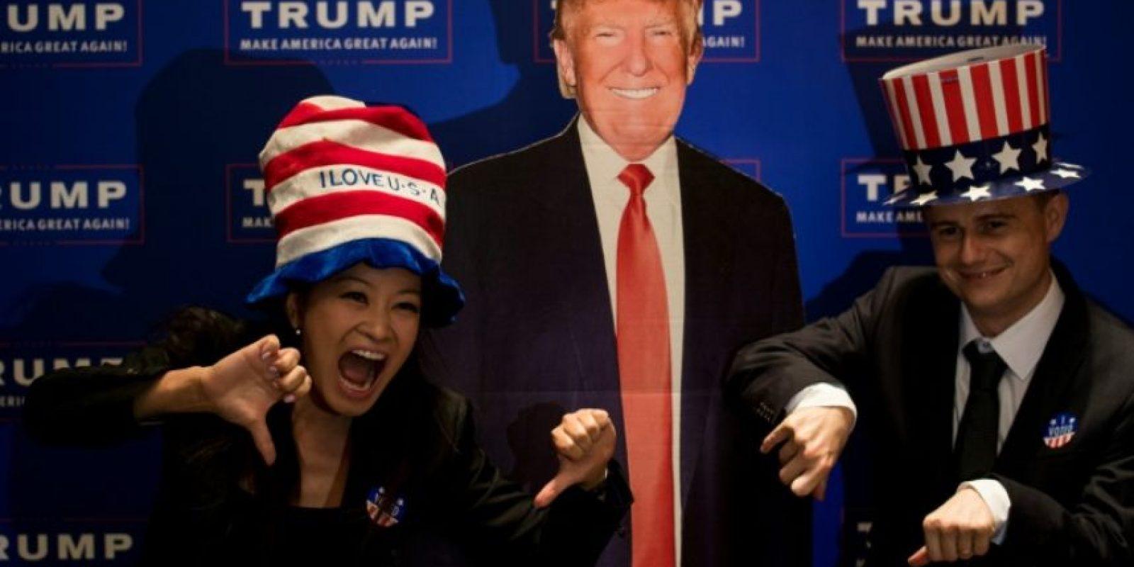Una pareja posa junto a una imagen de Donald Trump, el 9 de noviembre de 2016 en el Consulado de EEUU en Shangái Foto:Johannes Eisele/afp.com