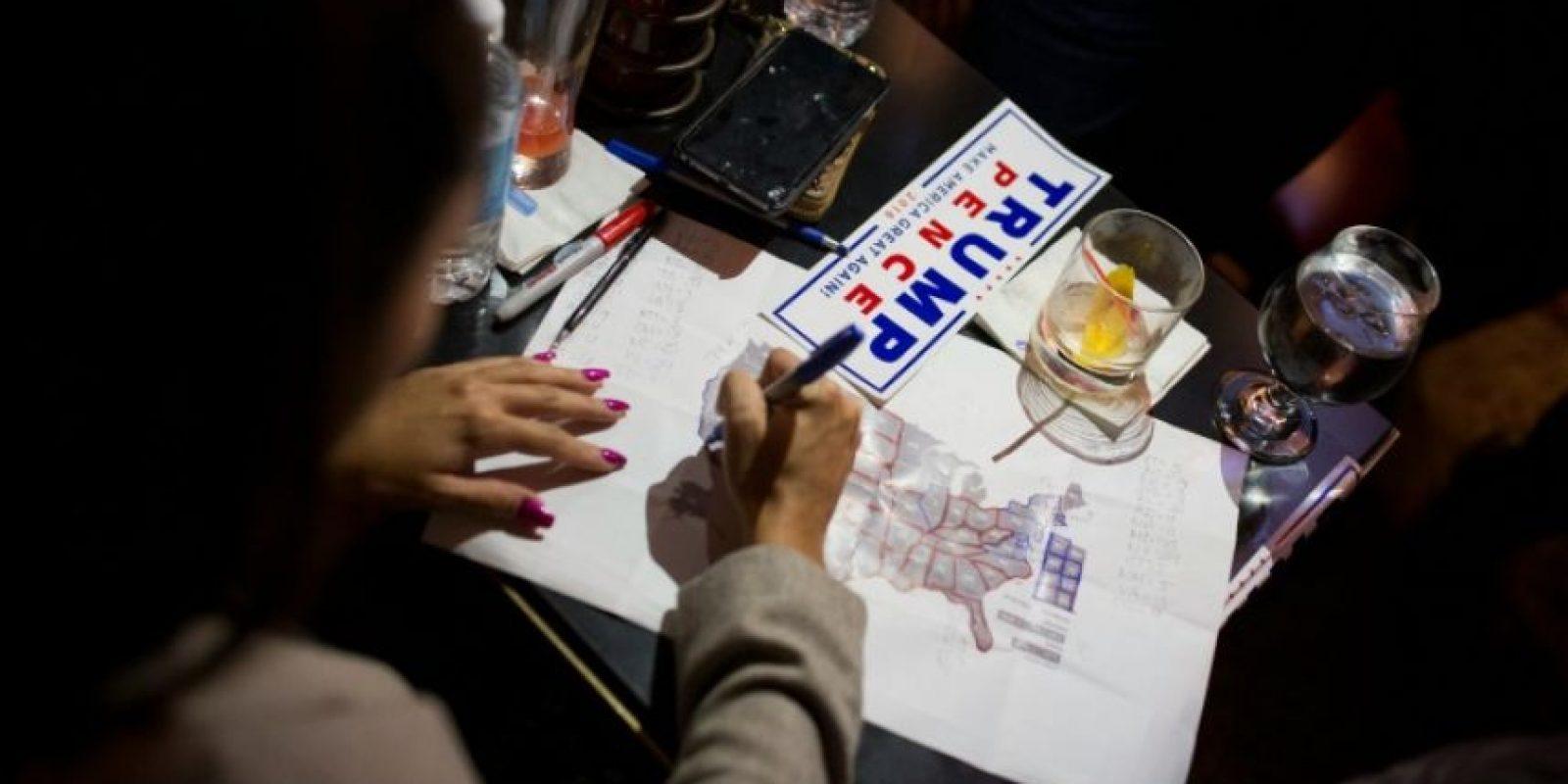 Una partidaria del presidente electo Donald Trump dibuja en un mapa de EEUU el 9 de noviembre de 2016 en el Trump Bar de Nueva York Foto:Dominick Reuter/afp.com