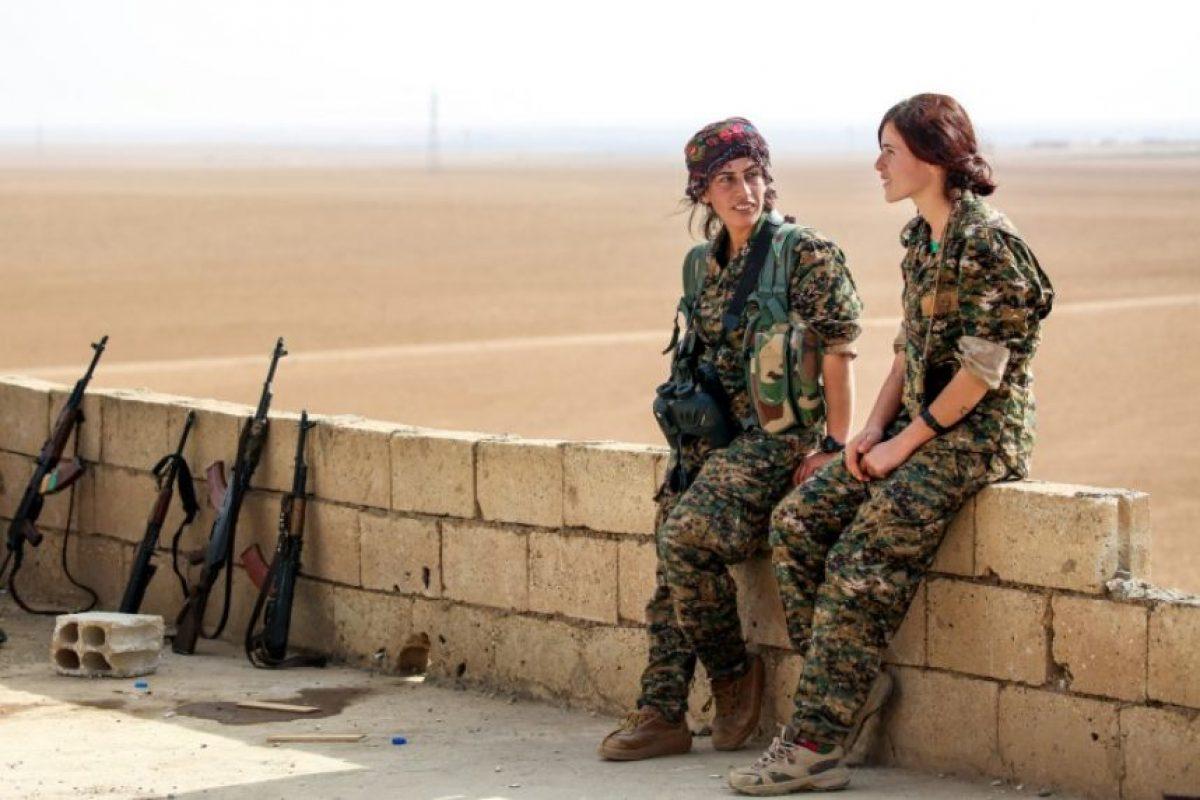 Shirin (I) y Kazîwar (D), combatientes de la Unidad de Protección Popular, conversan en una azotea en el pueblo sirio de Mazraat Jaled, a 40 kilómetros de Raqa, capital de facto del grupo Estado Islámico, el 9 de noviembre de 2016 Foto:Delil Souleiman/afp.com