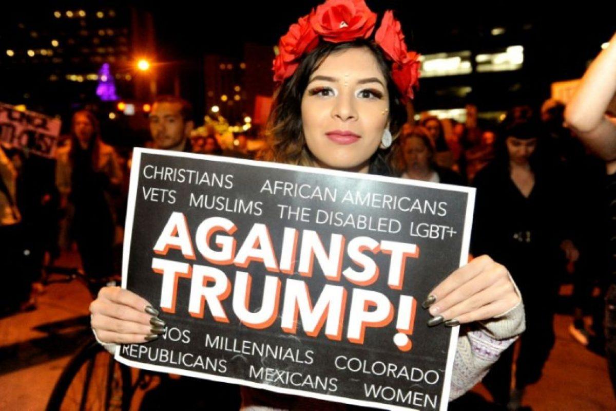 Una mujer sostiene un cartel con la leyenda 'Contra Trump' durante una manifestación contra el ganador de las elecciones presidenciales, Donald Trump, el jueves 10 de noviembre en Denver (centro de EEUU) Foto:Jason Connolly/afp.com