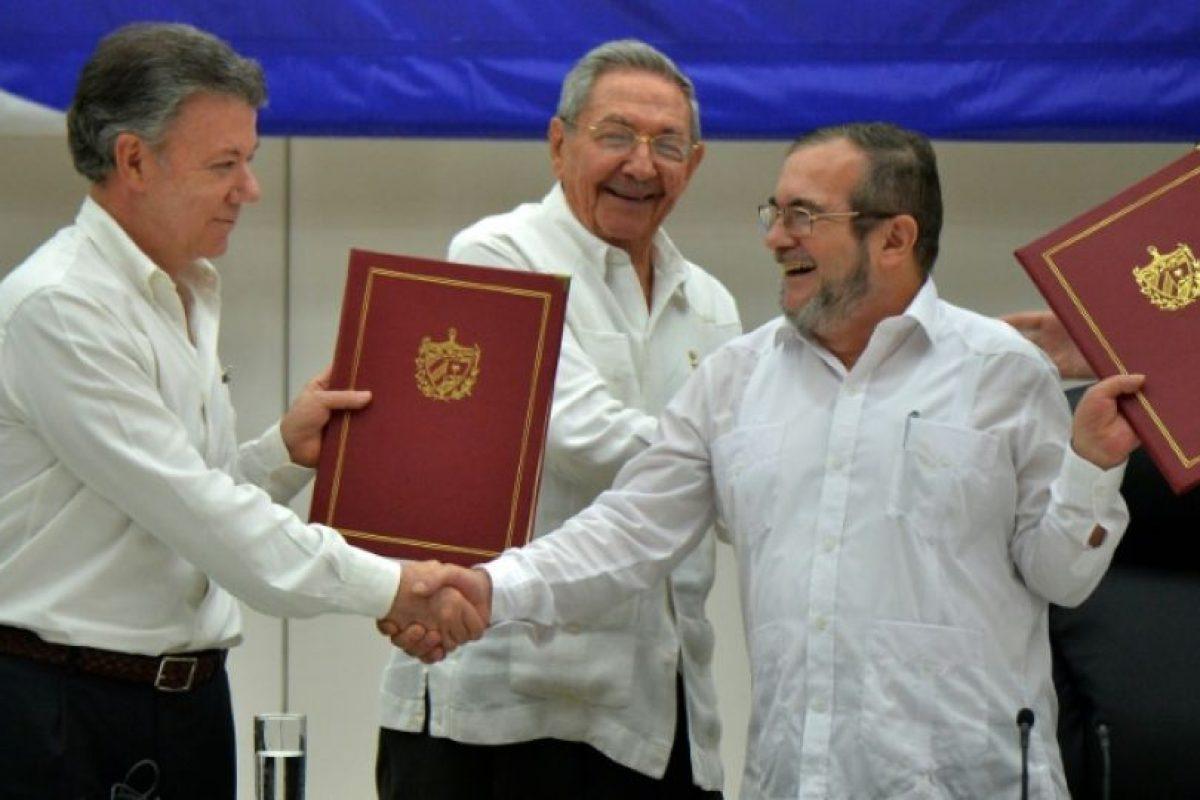 El presidente de Colombia, Juan Manuel Santos (I), estrecha la mano del jefe de las FARC Timoleón Jiménez, alias 'Timochenko', el 23 de junio de 2016 en La Habana, al firmar el alto el fuego Foto:Adalberto Roque/afp.com