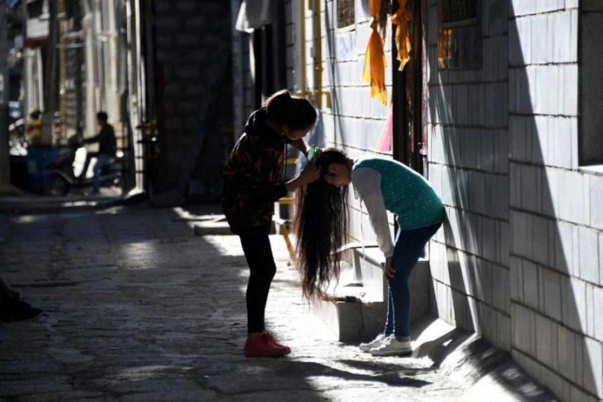 Una niña peina a otra en el barrio de Bayi, en Lhasa, capital de la región autónoma china de Tíbet, el 10 de septiembre de 2016 Foto:Johannes Eisele/afp.com