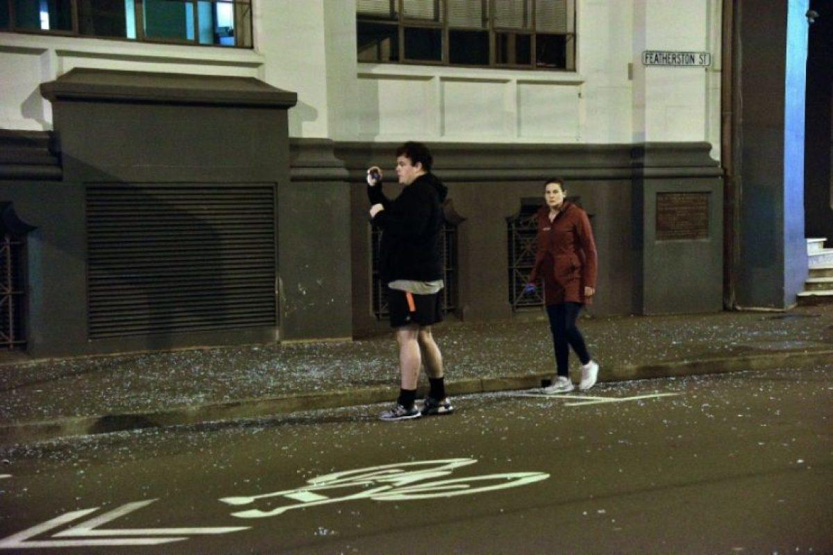 Dos personas salen a la calle en Wellington, con cristales rotos por el suelo, el 14 de noviembre de 2016, tras el terremoto Foto:Marty Melville/afp.com