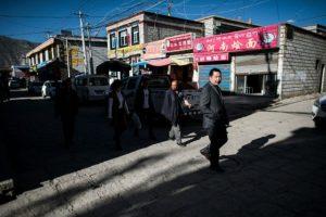 Varias personas caminan por una calles del barrio de Bayi, en Lhasa, capital de la región autónoma china de Tíbet, el 10 de septiembre de 2016 Foto:Joahnnes Eisele/afp.com