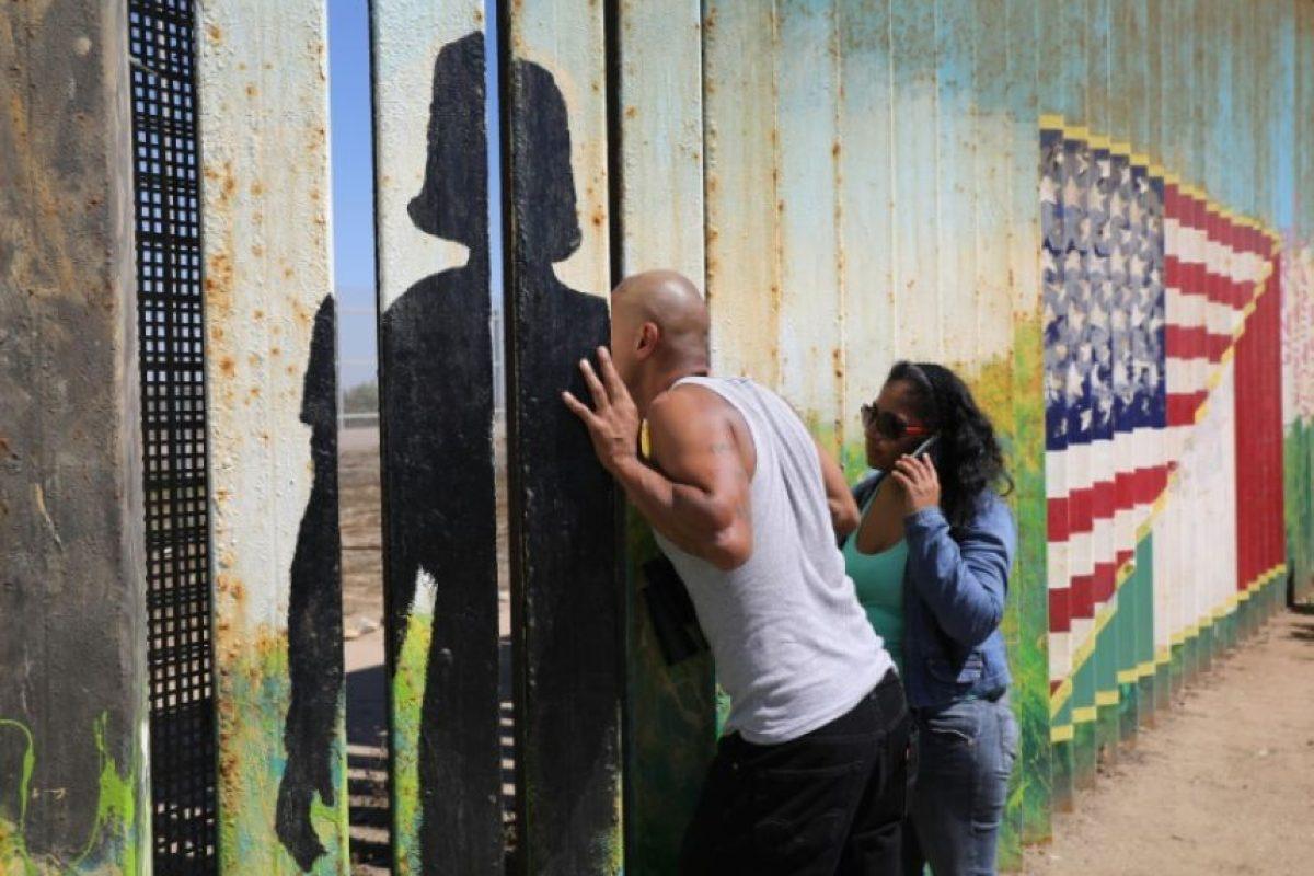 Un deportado en México habla a través de la cerca de la frontera Estados Unidos-México con familiares del lado estadounidense, el 25 de septiembre de 2016, en Tijuana, México. Foto:JOHN MOORE/afp.com