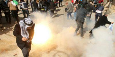 Manifestantes se cubren de humo mientras soldados israelíes disparan granadas y gas lacrimógeno durante enfrentamientos tras una manifestación contra los asentamientos judíos y el cierre de la calle al-Shuhada, el 20 de febrero de 2016, en la ciudad cisjordana de Hebrón. Foto:HAZEM BADER/afp.com