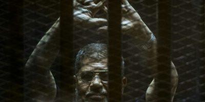 El derrocado presidente de Egipto Mohamed Mursi levanta los brazos en el interior de una celda de acusados durante un juicio en la academia de policía a las afueras de El Cairo el 2 de junio de 2015 Foto:Khaled Desouki/afp.com