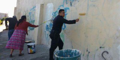 Policías borran las pintas de pandilleros en los muros de un colegio en Chimaltenango
