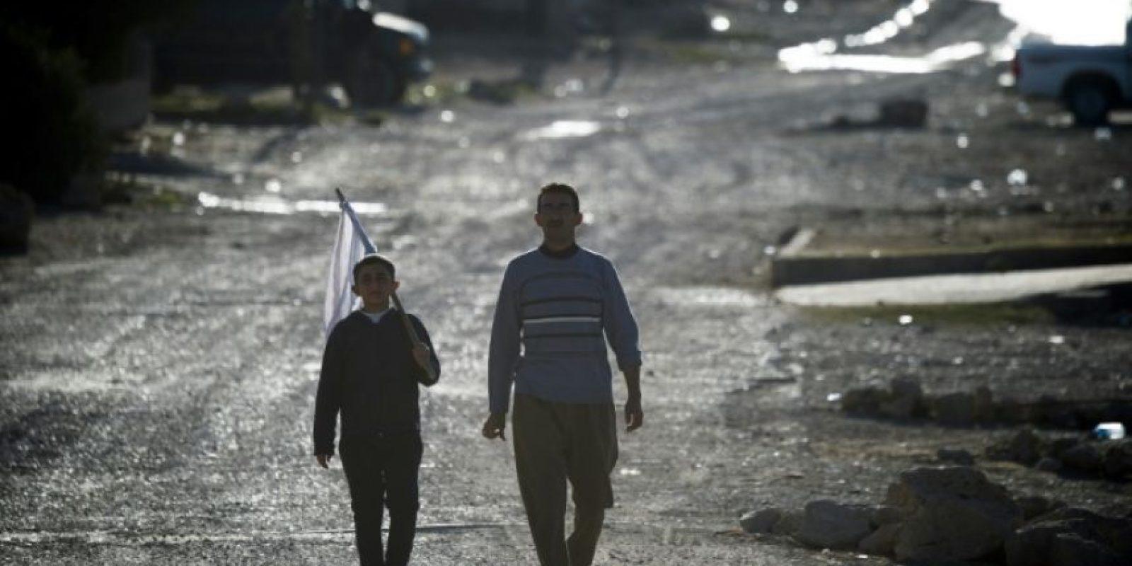 Un niño con una bandera blanca en señal de que es pacífico y su padre se acercan a las fuerzas de élite iraquíes en Tal Adh-Dhahab, unos 10 kilómetros al sur de Mosul el 19 de noviembre de 2016 Foto:Odd Andersen/afp.com