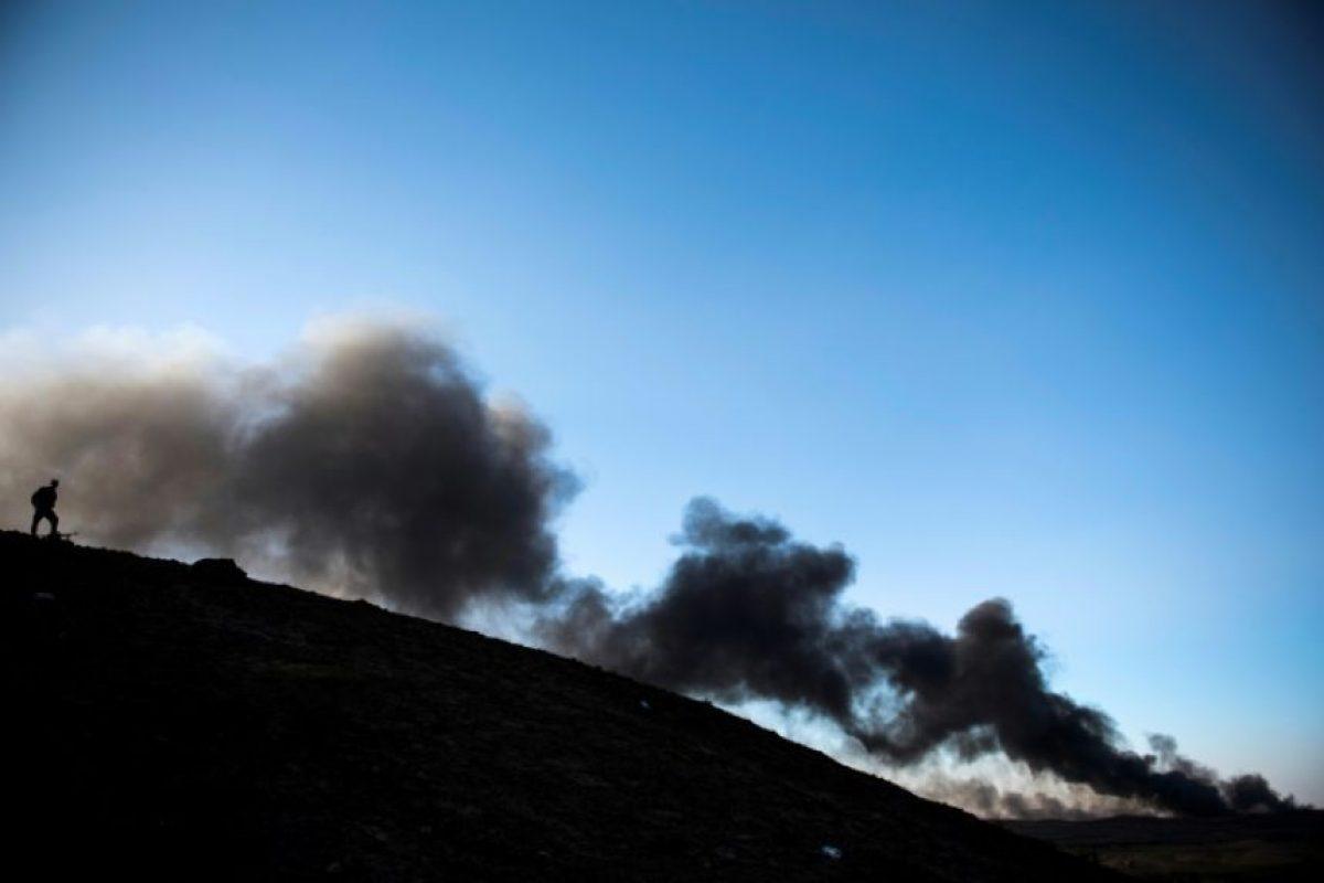 Un soldado iraquí vigila mientras bomberos e ingenieros intentan apagar el incendio de un pozo petrolero provocado por el grupo yihadista Estado Islámico (EI) al retirarse de una zona de Qayarah, al sur de Mosul, el 20 de noviembre de 2016 Foto:Odd Andersen/afp.com