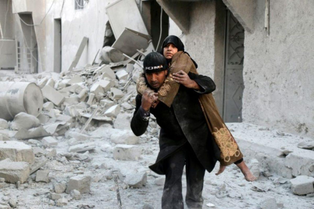 Un socorrista carga a hombros a una mujer rescatada entre los escombros de un edificio tras unos ataques aéreos contra el barrio en manos rebeldes de Al Hamra, al este de Alepo, el domingo 20 de noviembre en esa ciudad al norte de Siria Foto:Thaer Mohammed/afp.com