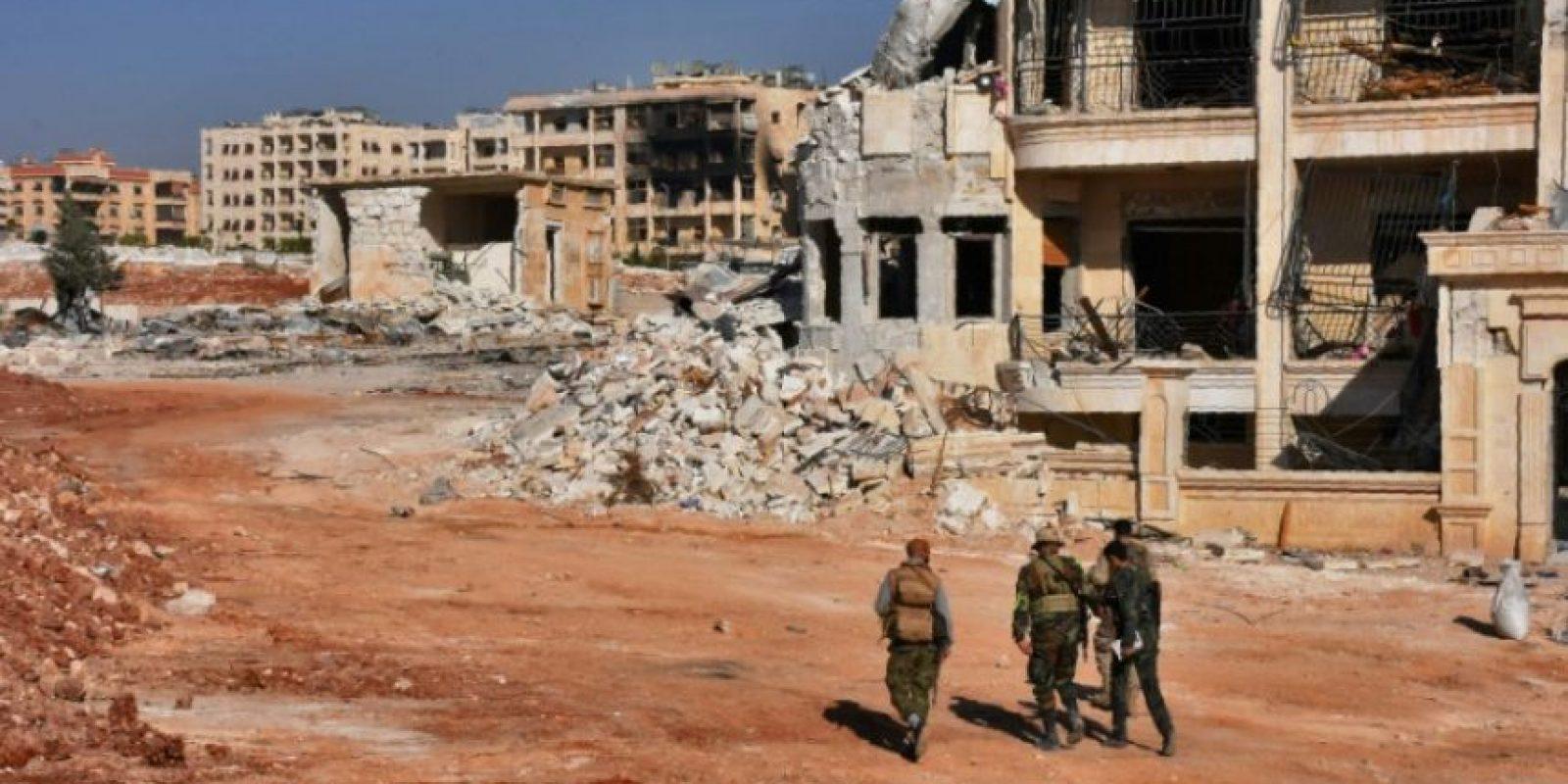 Miembros de las fuerzas progubernamentales de Siria caminan por una zona destruida en el barrio de Minyan, al oeste de Alepo, el pasado 10 de noviembre Foto:George Ourfalian/afp.com