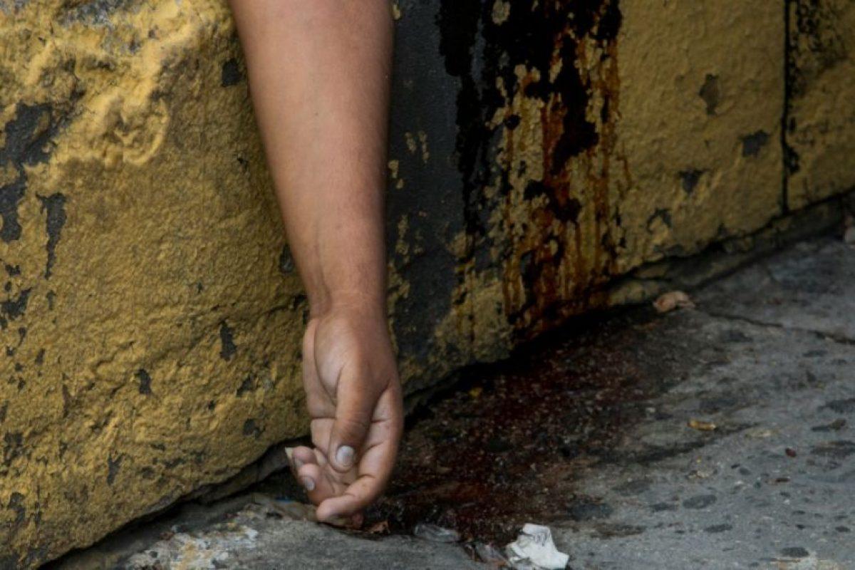 El cadáver de un hombre asesinado yace en una acera en la ciudad de Acapulco, estado de Guerrero, México, el 29 de agosto de 2016. Foto:PEDRO PARDO/afp.com