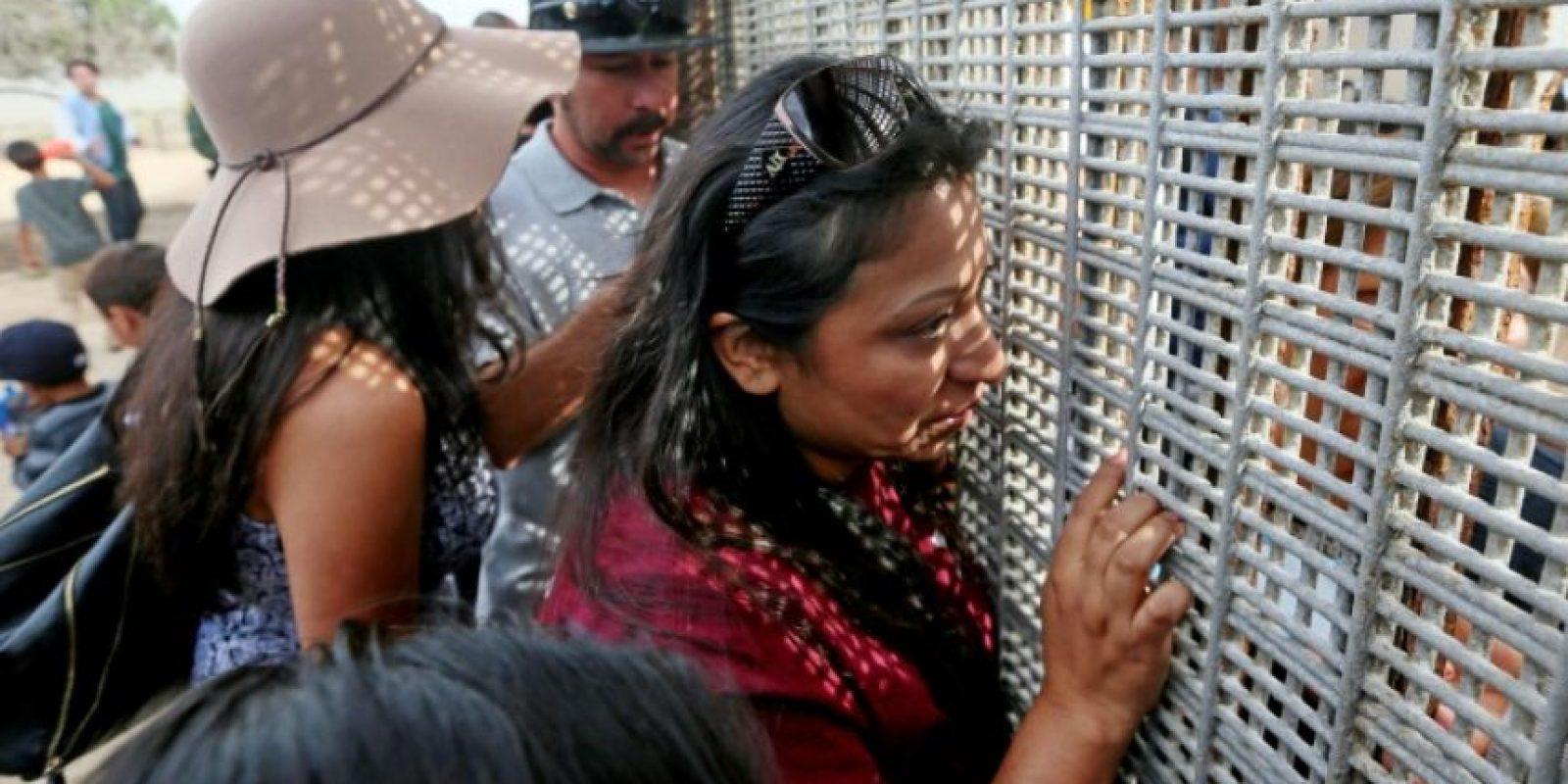Laura Ávila habla con miembros de su familia a través de la valla que separa México de Estados Unidos el 19 de noviembre de 2016 en San Ysidro Foto:Sandy Huffaker/afp.com