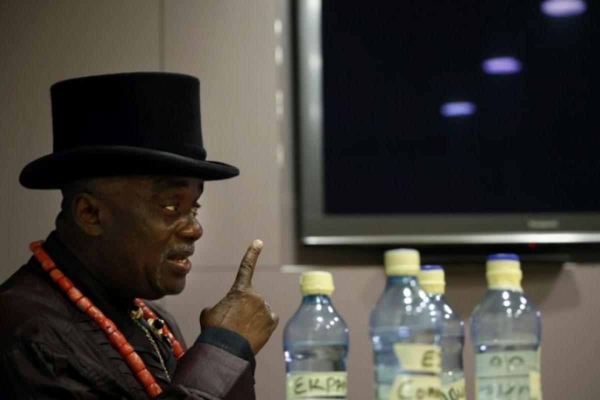 El rey tribal nigeriano Emere Godwin Bebe Okpabi habla durante una entrevista, en el centro de Londres, al lado de las muestras del agua contaminada, el 21 de noviembre de 2016 Foto:Adrian Dennis/afp.com