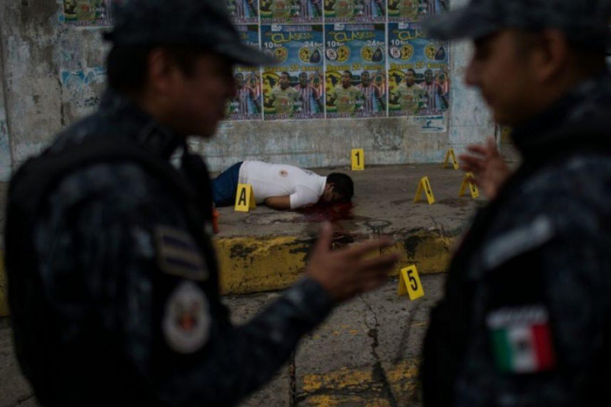 Policías federales hablan junto al cadáver de un hombre asesinado en Acapulco, estado de Guerrero, México, el 29 de agosto de 2016. Foto:Pedro Pardo/afp.com