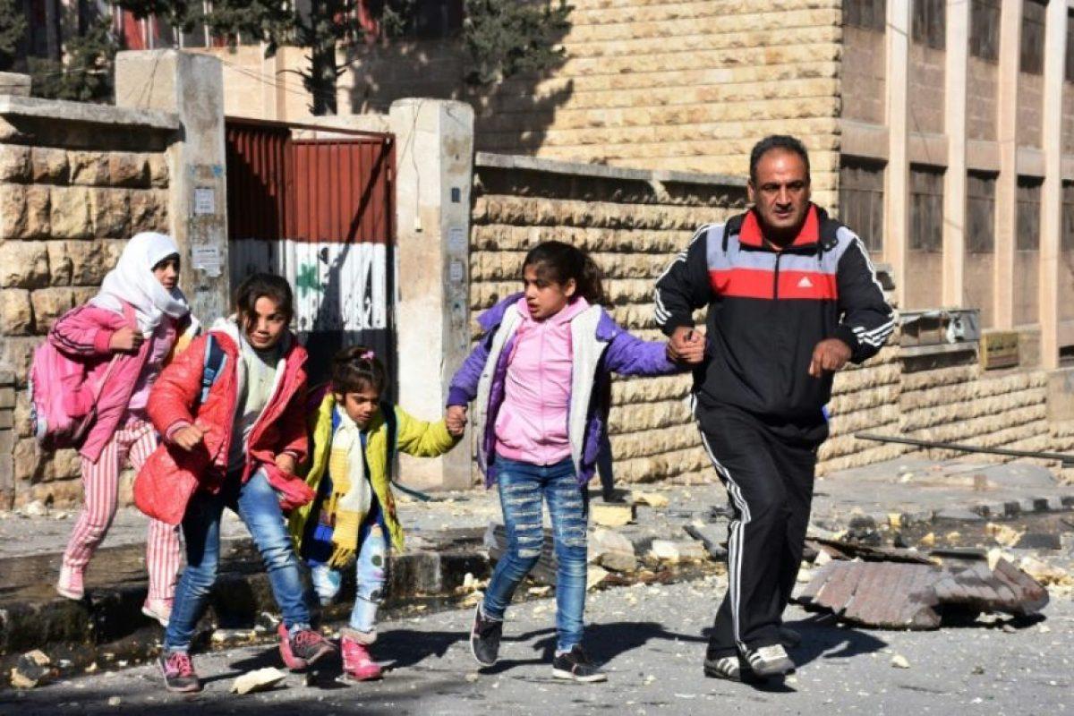 Un hombre evacua a varios niños de una escuela bajo fuego rebelde en el barrio de Furqan, en manos del régimen, el 20 de noviembre de 2016 en la ciudad siria de Alepo Foto:George Ourfalian/afp.com