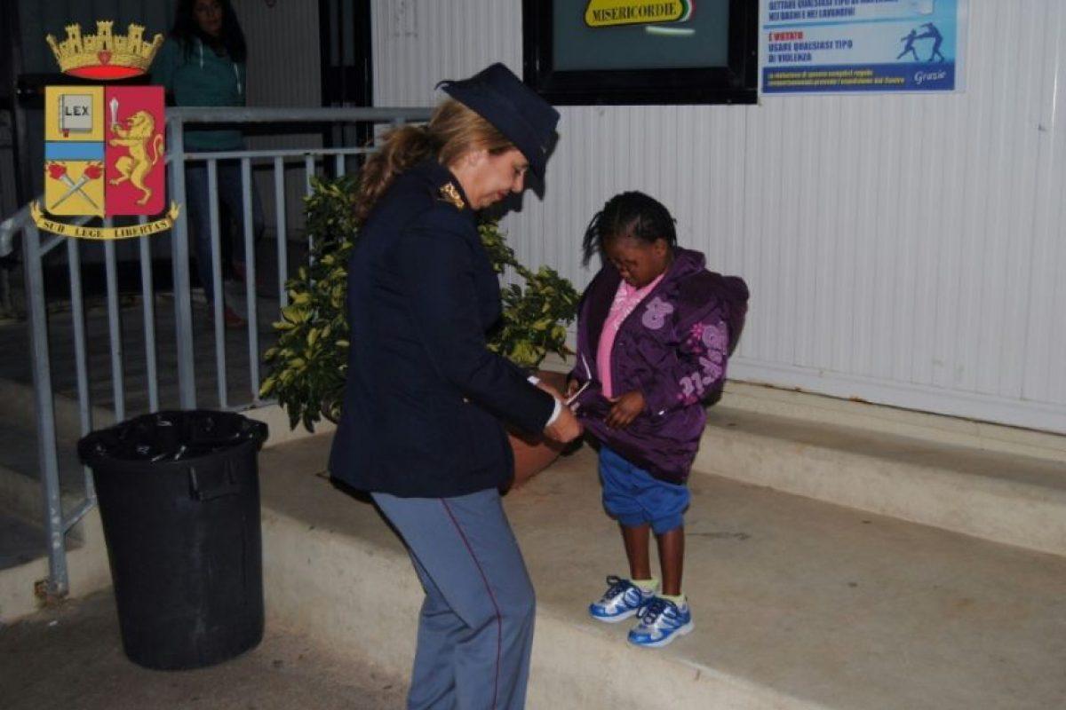 La policía italiana Maria Volpe, conocida como 'Mamma Maria', ayuda a la niña marfileña Oumoh, de 4 años, a vestirse, en una imagen distribuida por la policía el 23 de noviembre de 2016, en Agrigento Foto:HO/afp.com