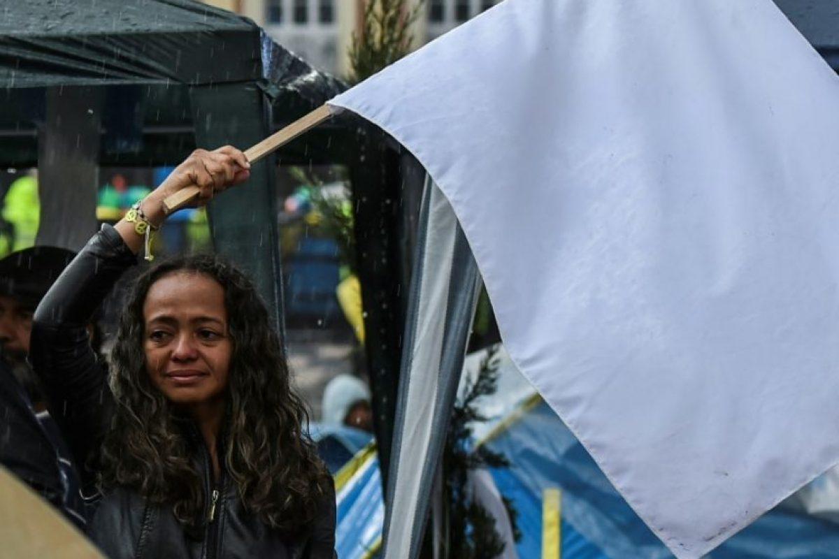 Una mujer llora mientras ondea una bandera durante una protesta para la implementación inmediata del acuerdo entre el Gobierno colombiano y las FARC, en la Plaza Bolívar de Bogotá, el 18 de noviembre de 2016 Foto:Luis Acosta/afp.com